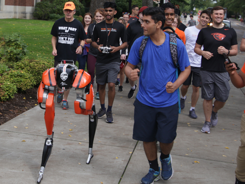 group of people walking alongside a 2 legged robot on campus